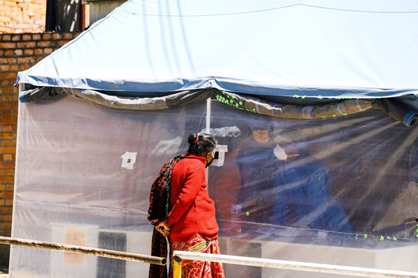 Woman looking into tent covered in plastic, covid-19 test